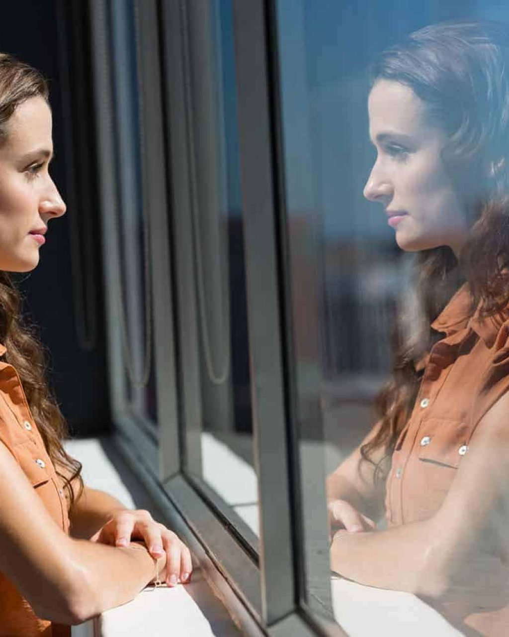 Side view of thoughtful businesswoman looking through window in office